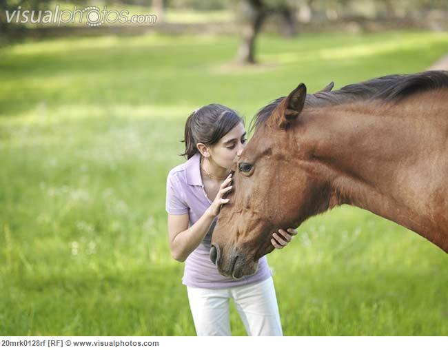 Girl kissing horse on forehead